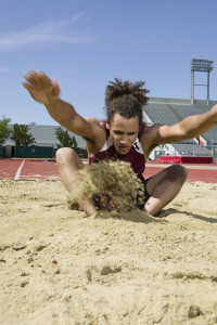 Male long jumper landing in sand pit